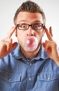 Man blowing a bubble using chewing gum.
